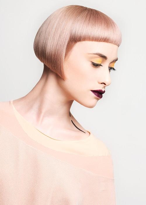 caschetto geometrico con frangia corta arrotondata dal colore rosa nude, modella con pelle molto chiara, make-up sulle labbra viola scuro mentre gli occhi hanno un'ombretto giallo